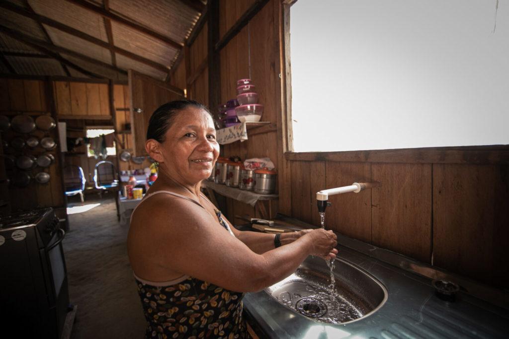Indígena exibindo cozinha com sistema de água encanada e pia instalada. Foto: Daniel Govino.